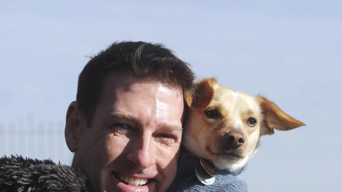 """In this Saturday, Jan. 19, 2013 photo, Michael Wright and his dog Toby pose for a portrait in New York.  Toby, previously named Fumble, last year's Animal Planets' """"Puppy Bowl"""" MVP winner, was adopted before the show aired. Wright said he found out about Fumble's participation toward the end of the adoption process, and plans to watch this year's show to catch any flashbacks of last year's MVP playing his heart out. (AP Photo/Mary Altaffer)"""