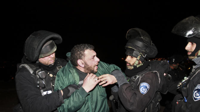 Israeli border policemen evict a Palestinian activist from an area known as E1 near Jerusalem, Sunday, March 24, 2013. Palestinian activists erected tents in the E1 area to protest Israeli plans for a new settlement in the area. (AP Photo/Nasser Shiyoukhi)