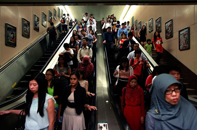SINGAPORE - FEBRUARY 13:  Commuters walk down escalators inside the Raffles Place MRT station during rush hour at the central business district area on February 13, 2013 in Singapore. The government white paper revealed Singapore's population may increase 30% to over 6.9 million by 2030, with nearly half the population expected to be foreign-born. Many local residents are critising the plan concerned about the added strain on housing, transportation and healthcare and the diminishing identity of the Singaporean community.  (Photo by Nicky Loh/Getty Images)