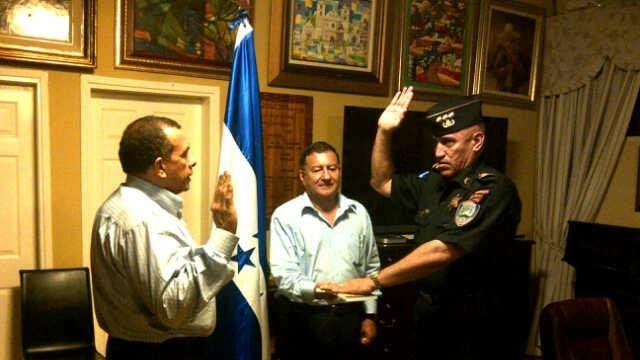 """In this May 22, 2012 photo released by the the presidential press office, Juan Carlos Bonilla Valladares, right, known as """"El Tigre"""" or """"The Tiger,"""" is sworn-in as Honduras' chief of police by President Porfirio Lobo, left, in Tegucigalpa, Honduras. Bonilla Valladares, the new chief chosen to clean up a Honduran national police force tarred with allegations of corruption and involvement in murders was accused by the department's internal affairs investigators of running a death squad when he was a top regional police official. (AP Photo/Honduras' Presidential Press Office)"""