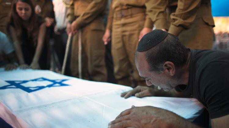 The father of Israeli soldier Tal Yifrah mourns over his son's flag-covered coffin during his funeral in Rishon Lezion near Tel Aviv