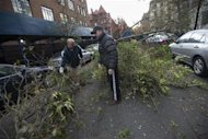 People try to clear branches from the street where a tree fell due to winds from Hurricane Sandy in the Brooklyn Borough of New York, October 31, 2012. REUTERS/Keith Bedford