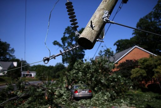 <p>Power lines hang from a utility pole snapped in half and a fallen tree covers a car on Yorktown Blvd. after heavy storms in the Washington, DC region June 30 in Arlington, Virginia. Utility crews made slow progress Sunday in restoring electricity to millions of households amid a record-setting heatwave in the eastern United States that showed no sign of abating soon.</p>