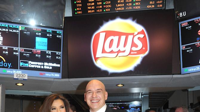 """IMAGE DISTRIBUTED FOR FRITO-LAY - Actress Eva Longoria and Chef Michael Symon join the Lay's brand at the New York Stock Exchange, Tuesday, Feb. 12, 2013, in New York, to introduce the three Lay's """"Do Us A Flavor"""" contest finalist flavors - Lay's Cheesy Garlic Bread, Lay's Chicken & Waffles and Lay's Sriracha flavored potato chips - now available on store shelves nationwide. (Photo by Diane Bondareff/Invision for Frito-Lay/AP Images)"""