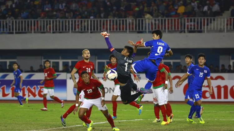 Kraisorn of Thailand and Indonesia's goalkeeper Hermansyah jump for the ball during their men's final soccer match at 27th SEA Games in Naypyitaw