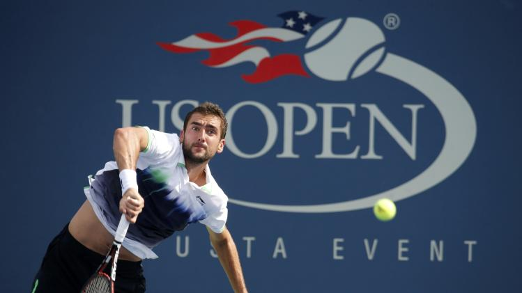Cilic of Croatia serves to Simon of France during their fourth round match at the 2014 U.S. Open tennis tournament in New York