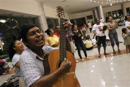 A man plays the guitar for people camping out at a shelter in Acapulco