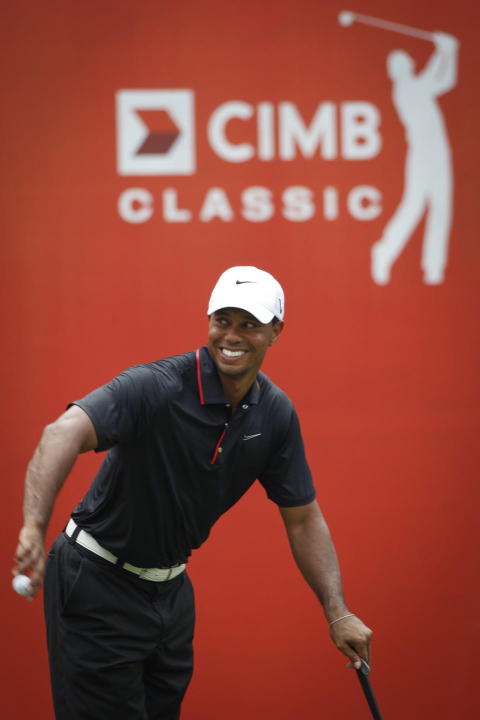 Tiger Woods of the United States smiles on the 18th hole during round two of CIMB Classic golf tournament at the Mines Resort and Golf Club in Kuala Lumpur, Malaysia, Friday, Oct. 26, 2012. (AP Photo/Vincent Thian)
