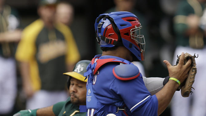 Oakland Athletics' Coco Crisp, left, scores behind Texas Rangers catcher Tomas Telis in the third inning of a baseball game Thursday, Sept. 18, 2014, in Oakland, Calif. Crisp scored on a triple by Oakland's Sam Fuld. (AP Photo/Ben Margot)