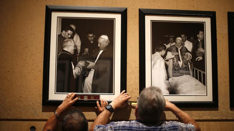 Workmen hang photos in a chapel created to honor the canonization of Popes John Paul II and John XXIII at the Cathedral of Our Lady of the Angels in Los Angeles