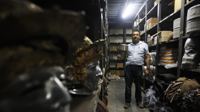 In this, June 2, 2012 photograph, Delhi businessman Ashok Rai, weapons and attire maker of war movies set from the 10th century to World War II, poses with a medieval helmet at his workshop in Sahibabad, India. From Hollywood war movies to Japanese Samurai films to battle re-enactments across Europe, Rai is one of the world's go-to men for historic weapons and battle attire. (AP Photo/Saurabh Das)