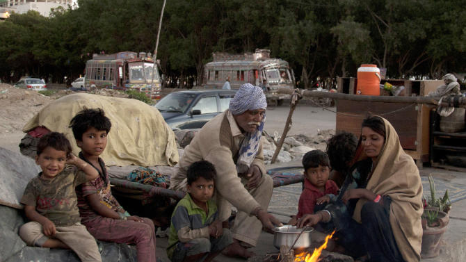 A homeless Pakistani family cooks on the side of a road roadside in Karachi, Pakistan, Monday, March 2, 2015. (AP Photo/Shakil Adil)