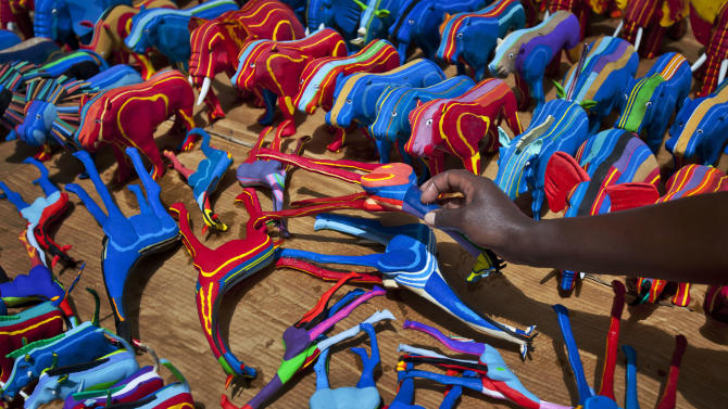 In this photo taken Monday, April 29, 2013, finished toy animals made from pieces of discarded flip-flops are laid out in rows to dry in the sun, having just been washed, at the Ocean Sole flip-flop recycling company in Nairobi, Kenya. The company is cleaning the East African country's beaches of used, washed-up flip-flops and the dirty pieces of rubber that were once cruising the Indian Ocean's currents are now being turned into colorful handmade giraffes, elephants and other toy animals. (AP Photo/Ben Curtis)