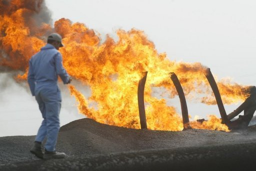 A man walks close to a flare at the North Rumaila oil field in southern Iraq. Iraq has insisted its oil output could reach up to 10 million barrels per day by 2020, far higher than a prediction from the International Energy Agency