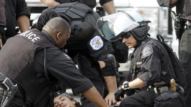 A protester is detained at a march and rally during this weekend's NATO summit in Chicago Sunday, May 20, 2012 in Chicago. (AP Photo/Seth Perlman)