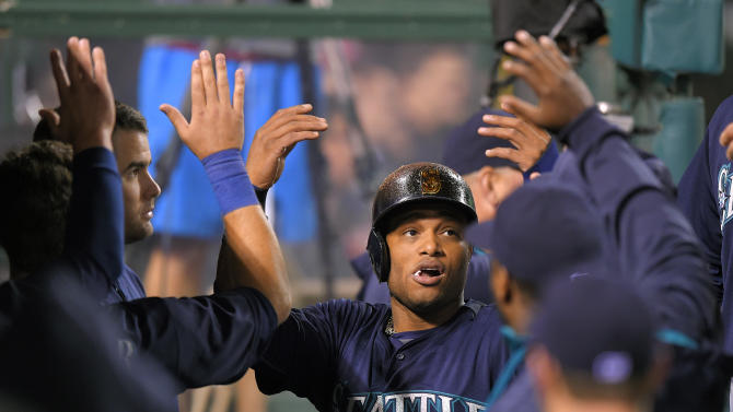 Seattle Mariners' Robinson Cano is congratulated by teammates after scoring on a single by Kyle Seager during the eighth inning of a baseball game against the Los Angeles Angels, Tuesday, May 5, 2015, in Anaheim, Calif. (AP Photo/Mark J. Terrill)