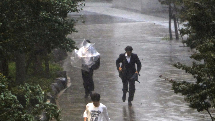People run in in the rain caused by Typhoon Roke in Tokyo, Wednesday, Sept. 21, 2011.  The storm, packing sustained winds of up to 100 mph (162 kph), made landfall in the afternoon near the central Japanese city of Hamamatsu, about 125 miles (200 kilometers) west of Tokyo. The storm was expected to cut a path northeast through the capital and into the northeastern region of Tohoku, which was devastated by the March 11 tsunami and earthquake. (AP Photo/Shizuo Kambayashi)