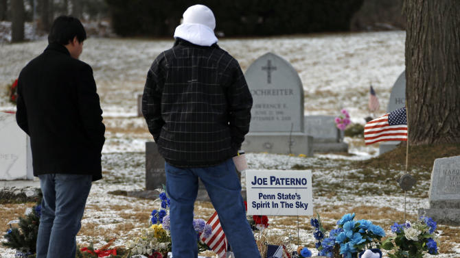 Penn State students Dan Hamm, left, a freshman from Williamsport, Pa., and Nick Bucci, a freshman from Dayton, Md., visit the grave of former Penn State head football coach Joe Paterno in State College, Pa. Supporters of Paterno are marking the 1-year anniversary of his death with a candlelight vigil Tuesday night.  (AP Photo/Gene J. Puskar)