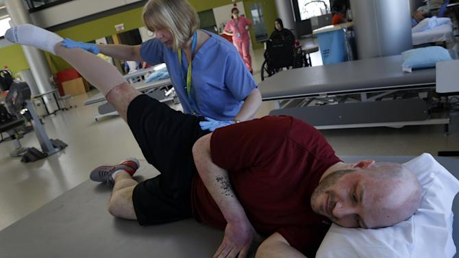 Boston Marathon bombing victim James Costello is stretched by Physical Therapist Lisa Pratt at Spaulding Rehabilitation Hospital in Boston's Charlestown section, Friday, May 10, 2013. (AP Photo/Elise Amendola)