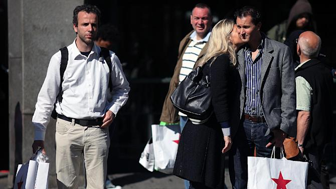 In this May 6, 2012 photo, people hold their purchases outside a Macy's in New York. Americans were more cautious about spending in May while their income increased only slightly, indicating the faltering job market has stoked fears about the economy's health. The Commerce Department says, on Friday, June 29, 2012, consumer spending showed no gain in May, the weakest figure since spending was unchanged in November. (AP Photo/CX Matiash)
