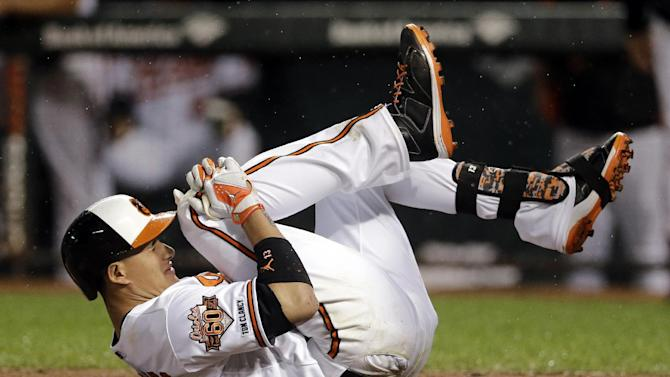 FILE - In this Aug. 11, 2014, file photo, Baltimore Orioles' Manny Machado holds his right knee after grounding out in the third inning of a baseball game against the New York Yankees in Baltimore. Machado left the game after getting hurt on the play. He will have season-ending surgery on his ailing right knee, the team announced Saturday, Aug. 23, 2014. (AP Photo/Patrick Semansky, File)