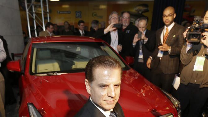 Cadillac Chief Engineer David Leone kneels in front of the Cadillac ATS which was named North American Car of the Year at the North American International Auto Show in Detroit, Monday, Jan. 14, 2013. (AP Photo/Carlos Osorio)