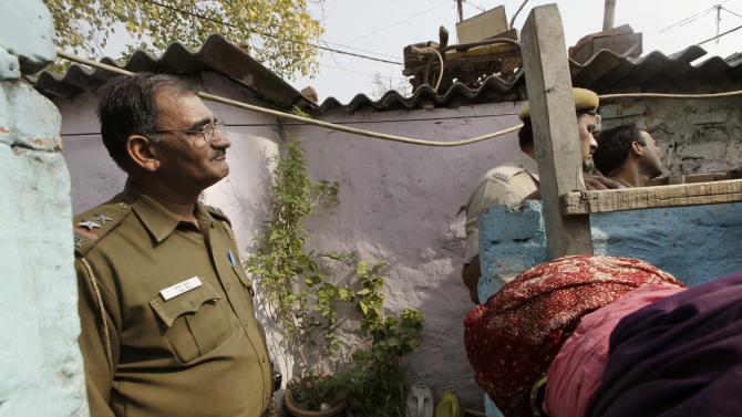 Delhi state police officers stand near the house of Ram Singh, the man accused of driving the bus on which the 23-year-old student was gang raped in December 2012, in New Delhi, India, Monday, March 11, 2013. Indian police confirmed that Ram Singh, one of the men on trial for his alleged involvement in the gang rape and fatal beating of a woman aboard a New Delhi bus committed suicide in an Indian jail Monday, but his lawyer and family allege he was killed.(AP Photo/Manish Swarup) INDIA OUT