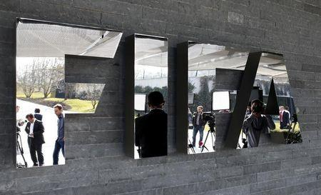 Journalists are reflected in the FIFA logo as they wait for a news conference after meeting of FIFA executive committee in Zurich