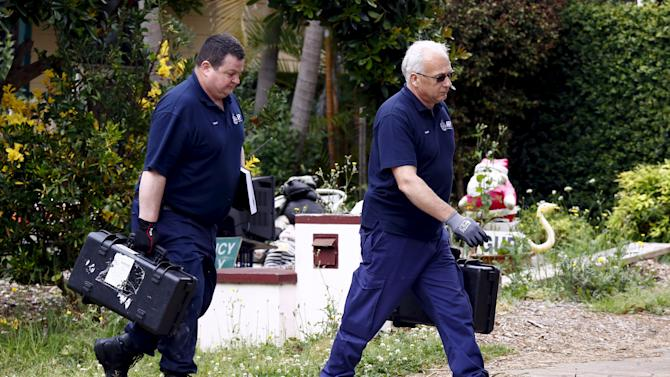 Federal police officers carry equipment into a house after arresting a man during early morning raids in western Sydney, Australia
