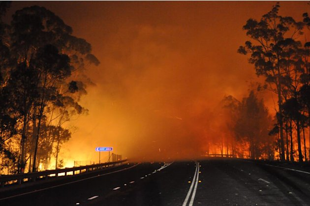 In this photo provided by the New South Wales Rural Fire Service a wildfire near Deans Gap, Australia, crosses the Princes Highway Tuesday, Jan. 8, 2013. Firefighters are battling scores of wildfires