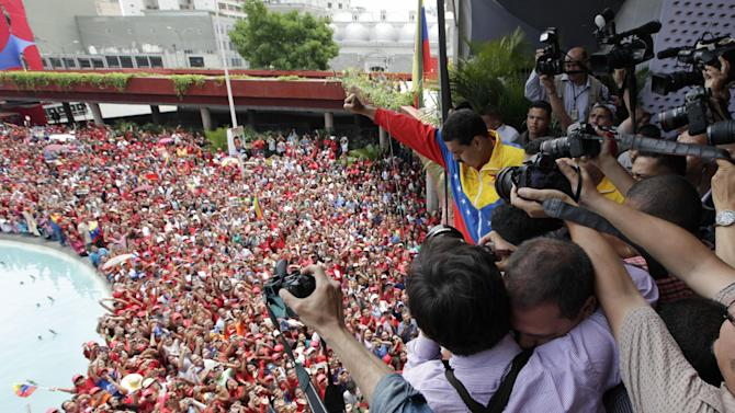 Photographer surround Venezuela's acting President Nicolas Maduro as he gestures to supporters after registering his candidacy for president to replace late President Hugo Chavez at the national electoral council in Caracas, Venezuela, Monday, March 11, 2013.  Elections were announced to take place on April 14, after the death of Chavez on March 5.  (AP Photo/Ariana Cubillos)