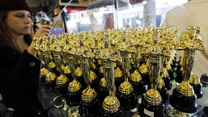 A woman photographs statuettes in the likeness of the Oscar award displayed across the street from the Hollywood and Highland complex ahead of Sunday night's Academy Awards in the Hollywood section of Los Angeles on Saturday, Feb. 23, 2013.  (AP Photo/Reed Saxon)
