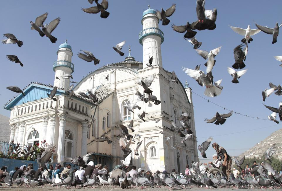 Pigeons fly outside Shah-e-Dushamshera's mosque where Afghans offer the Eid al-Fitr's prayers that marks the end of holy fasting month of Ramadan in Kabul, Afghanistan, Sunday, Aug. 19, 2012. (AP Photo/Musadeq Sadeq)