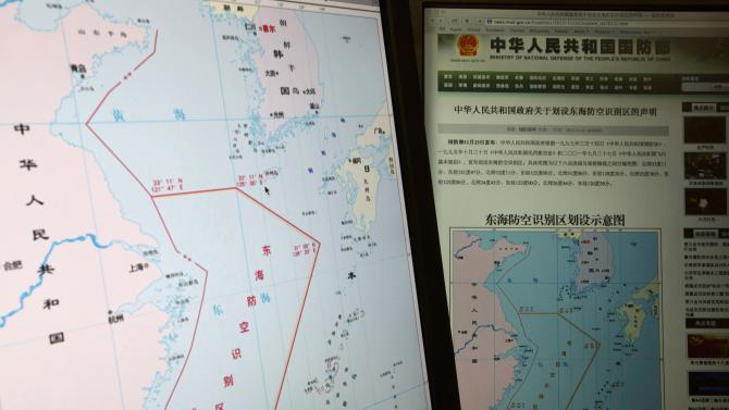 """Computer screens display a map showing the outline of China's new air defense zone in the East China on the website of the Chinese Ministry of Defense, in Beijing Tuesday, Nov. 26, 2013. Beijing on Saturday, Nov. 23, 2013 issued a map of the zone - which includes a cluster of islands controlled by Japan but also claimed by China - and a set of rules that say all aircraft entering the area must notify Chinese authorities and are subject to emergency military measures if they do not identify themselves or obey Beijing's orders. Chinese characters in red in the center of the map at left reads: """"Air Defense Identification Zone in East China Sea."""" (AP Photo/Ng Han Guan)"""
