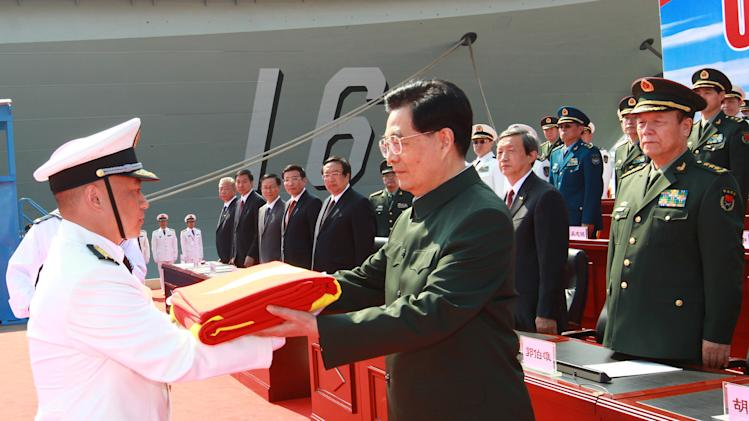 "In this photo provided by China's Xinhua News Agency, Chinese President Hu Jintao, center, endorses the flag of the People's Liberation Army (PLA) to the naval unit that receive the aircraft carrier ""Liaoning"" at the carrier handover ceremony at a naval base in Dalian, northeast China's Liaoning Province, Tuesday, Sept. 25, 2012.  China formally entered its first aircraft carrier Liaoning  into service on Tuesday, underscoring its ambitions to be a leading Asian naval power, although the ship is not expected to carry a full complement of planes or be ready for combat for some time.  (AP Photo/Xinhua, Zha Chunming) NO SALES"