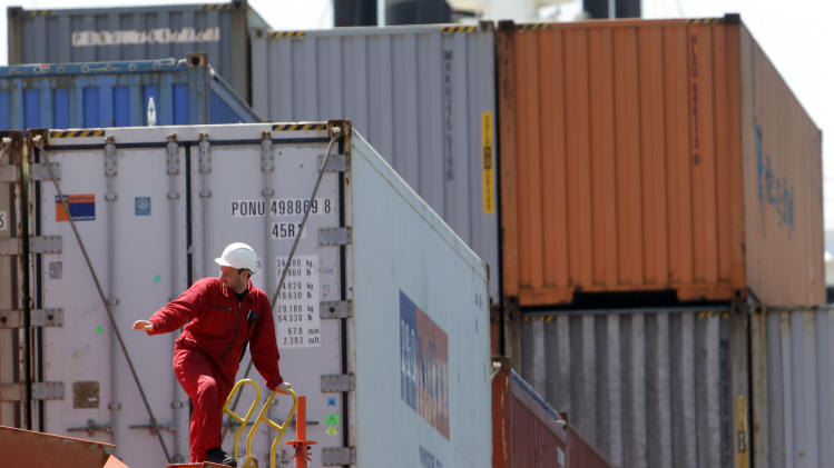 In this Tuesday, May 14, 2013 photo, a sailor on the Bahia Castillo, a Hamburg SUD-operated refrigerated cargo ship carrying fresh Chilean fruit and other goods, signals as it docks at Packer Avenue Marine Terminal, in Philadelphia. The U.S. trade deficit increased in May to the highest level in six months as a weak global economy depressed U.S. export sales while imports of autos and other nonpetroleum products hit an all-time high. (AP Photo/Matt Rourke)