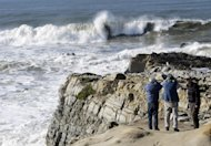 Visitors watch waves crash on a cliff in Pescadero, Calif., Thursday, Dec. 13, 2012. The National Weather Service says so-called King Tides  caused by a rather unique combination of how the sun, the moon and the earth align  will bring the highest tides of the year on Thursday, Friday and Saturday mornings. Along with the high tides, forecasters say a building swell will bring large breaking waves to area beaches. (AP Photo/Marcio Jose Sanchez)
