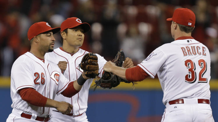 Cincinnati Reds outfielders Xavier Paul (26), Shin-Soo Choo, and Jay Bruce (32) celebrate after the Reds defeated the Washington Nationals 15-0 in a baseball game, Friday, April 5, 2013, in Cincinnati. Paul hit a grand slam in the game. (AP Photo/Al Behrman)