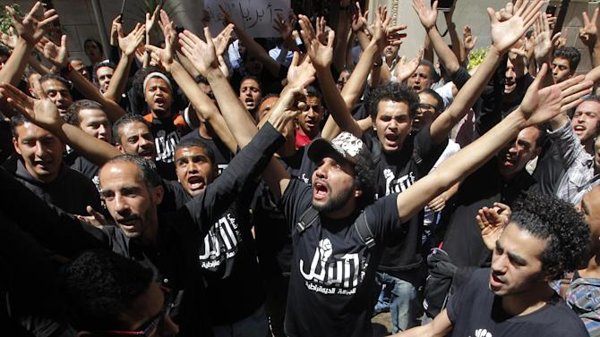 """Members of Egypt's April 6 Youth Movement shout anti-Muslim Brotherhood slogans during a rally in front of Cairo's stock market, in Cairo, Egypt, Saturday, April 6, 2013. The group is rallying to mark its fifth anniversary and to protest against President Mohammed Morsi. Arabic on T-shirts reads, """"6th April."""" (AP Photo/ Amr Nabil)"""