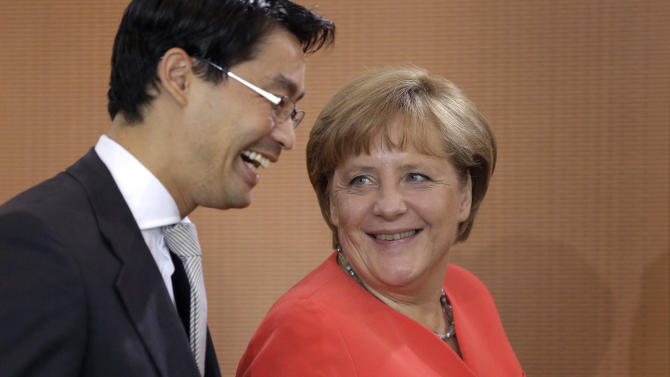 German Chancellor Angela Merkel, right, and German Economy Minister Philipp Roesler, left, arrive for the weekly cabinet meeting at the chancellery in Berlin, Germany, Wednesday, Aug. 22, 2012. (AP Photo/Michael Sohn)