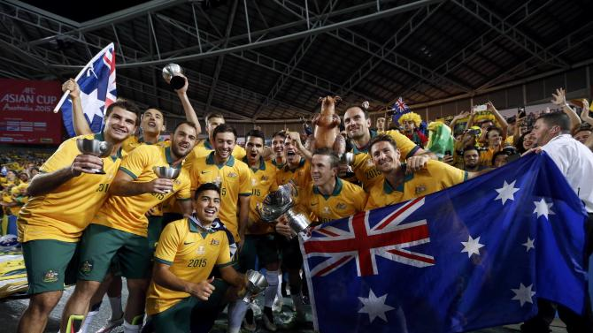 Australia's players pose for pictures with their trophies and the Asian Cup trophy after they beat South Korea to win the tournament at the Stadium Australia in Sydney