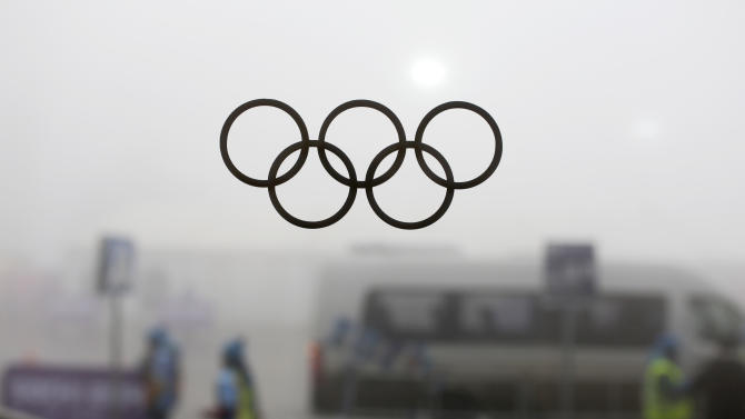 Olympic rings on a window are silhouetted against thick fog at the Laura Biathlon centre at the 2014 Winter Olympics, Monday, Feb. 17, 2014, in Krasnaya Polyana, Russia. The men's 15-kilometer mass-start biathlon race at the Sochi Olympics has been delayed due to fog, one day after the event had been called off for the same reason. (AP Photo/Felipe Dana)
