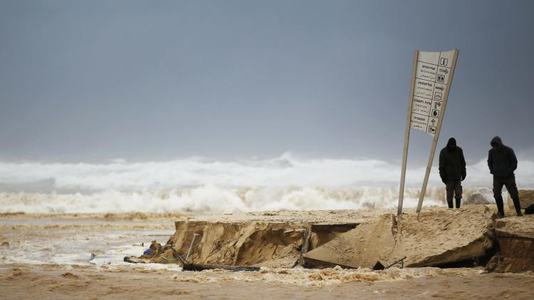 People look on the damage caused by a storm on a beach of the Mediterranean sea near Kibbutz Nitzanim