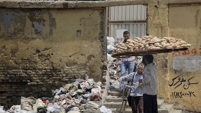 In this Thursday, Aug. 16, 2012 photo, a bread vendor and others walk in front of loads of garbage on a Cairo street. A government modernization effort flopped. A swine flu panic prompted the mass slaughter of the pigs that recycled Cairo's organic garbage; the city's metal trash bins were easy prey for thieves, especially during the global scrap metal boom. Now the garbage crisis in the Arab world's biggest city is posing a significant test for the newly elected government that replaced longtime autocratic leaders. (AP Photo)