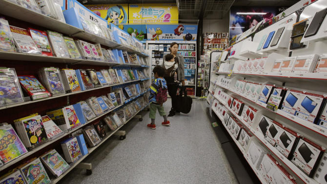 In this photo taken Sunday, Dec. 15, 2013, shoppers walk through the sales floor of Nintendo 3DS video game software at an electronics store in Tokyo. Nintendo Co. says its profit for the first nine months of the fiscal year fell 30 percent because of languishing sales of its Wii U home consoles and game software. The Japanese maker of Super Mario video games reported Wednesday, Jan. 29, 2014, a 10.2 billion yen ($99 million) profit from April to December, down from 14.55 billion yen a year earlier. It did not break down quarterly numbers. (AP Photo/Shizuo Kambayashi)