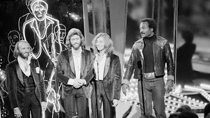 """FILE - In this Dec. 8, 1977, file photo, The Bee Gees, from left, Maurice, Barry and Robin Gibb, join actor Jim Brown, right, on Stage 14 of Paramount Studios during a disco party for the premiere of """"Saturday Night Fever"""" in Los Angeles. A representative said on Sunday, May 20, 2012, that Robin Gibb has died at the age of 62. (AP Photo/File)"""