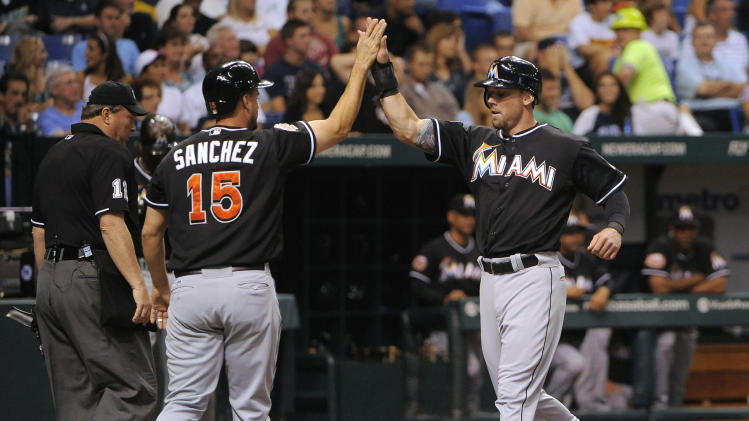 Miami Marlins' Gaby Sanchez, left, and Scott Cousins celebrate at the plate after scoring on Jose Reyes' single off of Tampa Bay Rays pitcher James Shields during the second inning of an interleague baseball game Saturday, June 16, 2012, in St. Petersburg, Fla. (AP Photo/Brian Blanco)