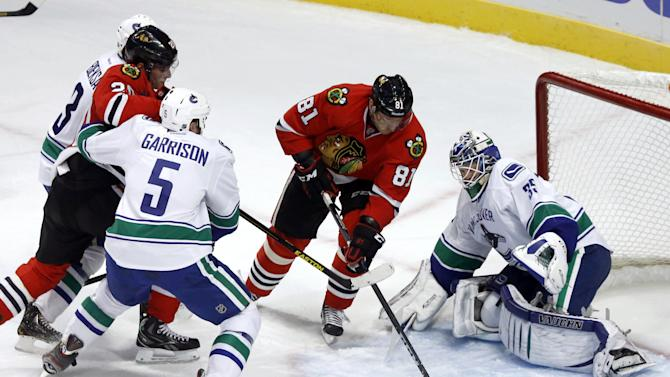 Chicago Blackhawks right wing Marian Hossa (81), from Slovakia, splits the defense of Vancouver Canucks' Kevin Bieksa (3), Jason Garrison (5) and goalie Cory Schneider to score his second goal in the second period of an NHL hockey game Tuesday, Feb. 19, 2013 in Chicago.  Blackhawks' Brandon Saad watches the play. (AP Photo/Charles Rex Arbogast)