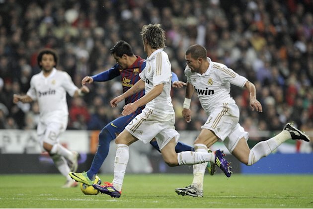 Barcelona's Alexis Sanchez from Chile, center left, scores against Real Madrid during his Spanish La Liga soccer match at the Santiago Bernabeu stadium, in Madrid, Saturday, Dec. 10, 2011. (AP Photo/D