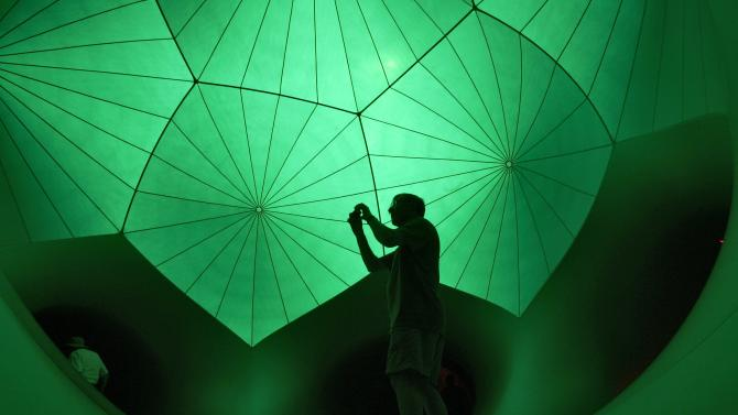 A man takes a photograph inside Exxopolis, an inflatable walk-in luminarium at Grand Park in Los Angeles, California